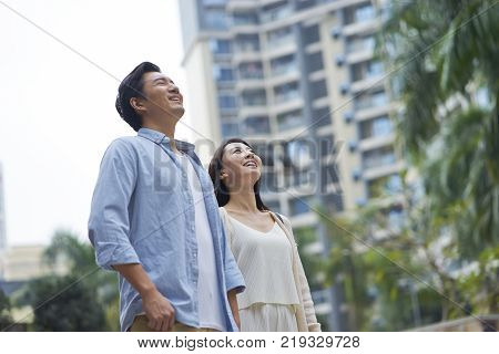 Asian couple  standing outdoors in garden looking up & smiling