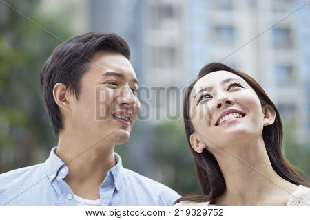 Asian couple standing outdoors in garden, smiling & looking up
