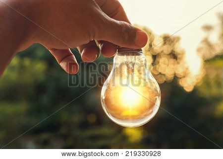 idea concept of power energy with hand holding light bulb and sunset in nature