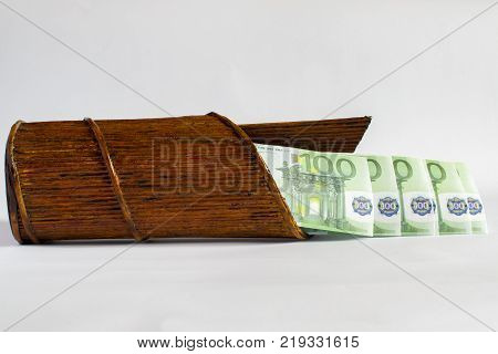 A paper tube similar to a wooden. Brown basket with large euro banknotes against a light background.