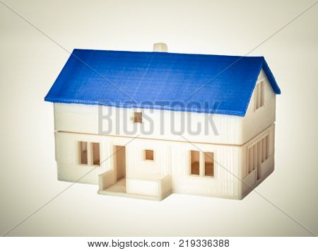 Objects printed by 3d printer Isolated on white background. White house with a blue roof. Progressive modern additive technology. Concept of 4.0 industrial revolution