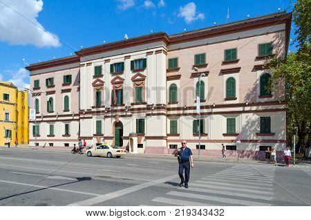 TIRANA ALBANIA - SEPTEMBER 6 2017: Unknown people walk along street near building of Ministry of Internal Affairs of Albania on boulevard of Martyrs in Tirana
