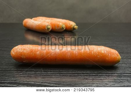 Raw fresh carrot on a wooden table.