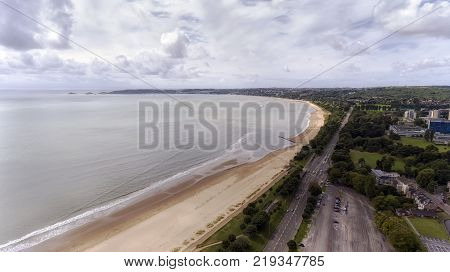 Editorial Swansea, UK - July 29, 2017: A view of Swansea West and the long stretch of sand swept Swansea Bay showing Oystermouth Road, Swansea University, Singleton Park and The Mumbles, .