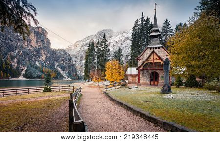 Little church on Braies Lake. Colorful autumn landscape in Italian Alps Naturpark Fanes-Sennes-Prags Dolomite Italy Europe. Artistic style post processed photo.
