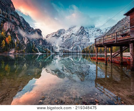 Boat hut on Braies Lake with Seekofel mount on background. Colorful autumn landscape in Italian Alps Naturpark Fanes-Sennes-Prags Dolomite Italy Europe. Artistic style post processed photo.