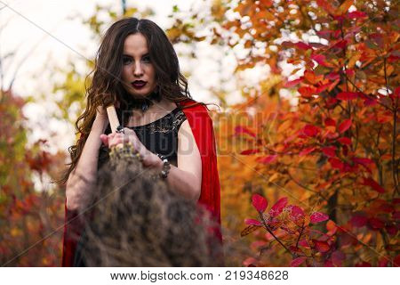 Young beautiful and mysterious woman is Prepare to Fight with Broom, in black Dress and Red Cloak, image of forest elf or witch