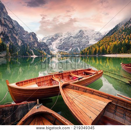 Pleasure boats on Braies Lakeand Seekofel mount on background. Colorful autumn landscape in Italian Alps Naturpark Fanes-Sennes-Prags Dolomite Italy Europe. Artistic style post processed photo.