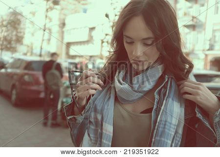 Beautiful brunette girl is walking in a city street. She is rearranging her scarf. She is wearing a blue jeans jacket. Holding sunglasses in her hand.