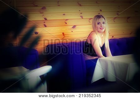 Beautiful blonde girl posing while sitting in a cozy cafe. She wears a black lace tops and blue jeans. The girl smiles sincerely. The table in the cafe is covered with a white tablecloth.