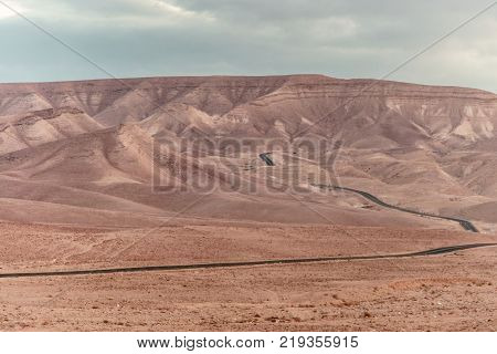 Colorful landscape view on judean desert land with magic blue sky on background and color clouds. Beautiful nature with mountains, rocks, sand and ruins in holy land in Israel.