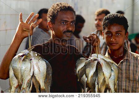 AL HUDAYDAH, YEMEN - SEPTEMBER 17, 2006: Unidentified Yemeni fisherman demonstrates catch of the day at the fish market in Al Hudaydah, Yemen.