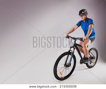 handsome cyclist portrait on a gray studio background