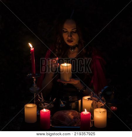 Young beautiful and mysterious Witch woman Provide Dark Ritual in woods With Detached Heart and Candles, image of forest elf or witch