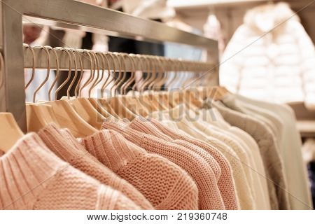 pink womens clothes on wood hangers on rack in fashion store . closet women sweaters close up