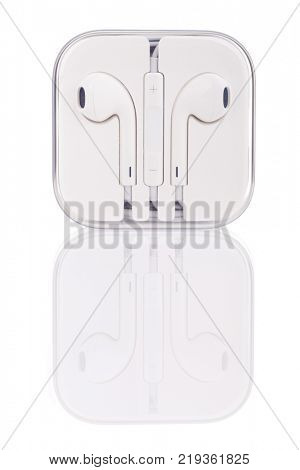 White headphones for smartphone in  transparent box with reflection, isolated
