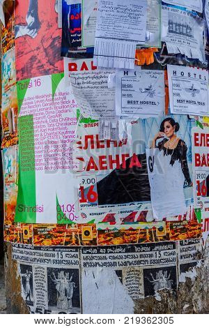 TBILISI, GEORGIA - OCTOBER 10: Colorful flyers and advertizing in different languages on a pillar in city center Tbilisi. October 2016
