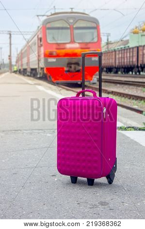Suitcase bag at railway station with the train as background