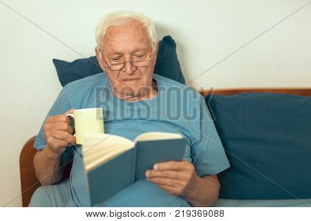 Senior man lying on bad and reading book at home