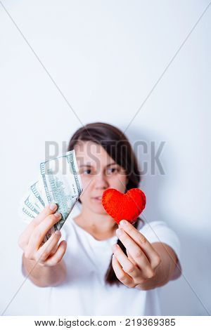 love or money concept woman hold heart and money in hands