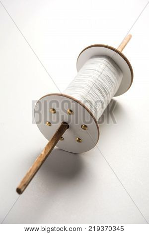 Wooden Spool or chakri/reel/fikri with pink or white thread, isolated over white background