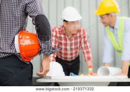 engineer and construction team wearing safety helmet and looking blueprint on the table. they are working on checking progress of construction site. engineer and client reviewing material and checking construction process in construction site area.