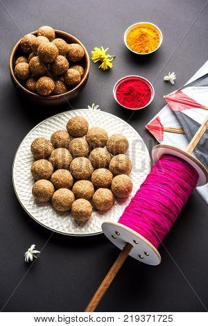 happy Makar Sankranti Festival - Tilgul or Til ladoo in a bowl or plate with haldi kumkum and flowers with Fikri /Reel/Chakri /Spool with colourful thread or manjha and kite over plain background