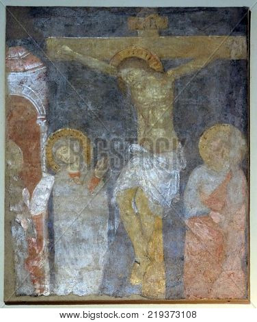 LUCCA, ITALY - JUNE 03: Crucifixion, Virgin Mary and Saint John under the Cross, fresco painting in Basilica of Saint Frediano, Lucca, Tuscany, Italy on June 03, 2017.
