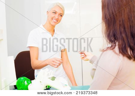 dental assistant checking her patient's health insurance card