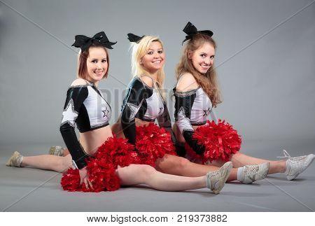 Studio shot of three cheerleaders doing the splits