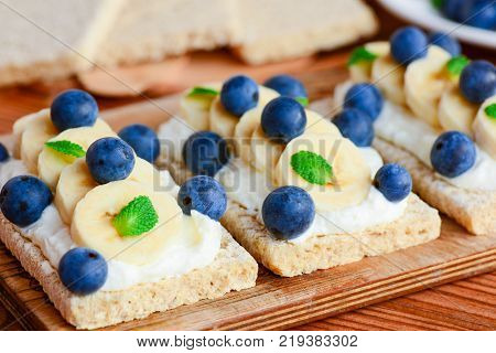 Crispbread toast with cottage cheese, banana and berries on wooden board. Cottage cheese open sandwich idea. Closeup