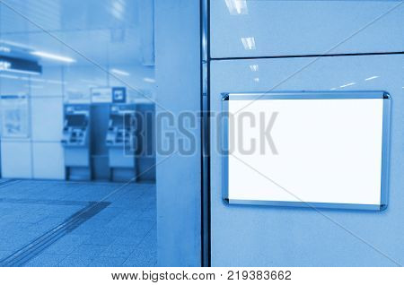 blank advertising billboard or light box showcase with ticket vending machine background at train station copy space for your text message or media content commercial marketing concept blue tone