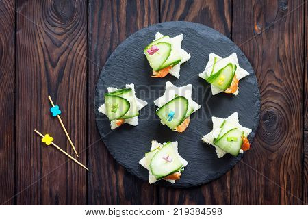 Appetizer Canape With White Bread, Cucumber, Ricotta And King Prawns On A Festive Table. Top View.