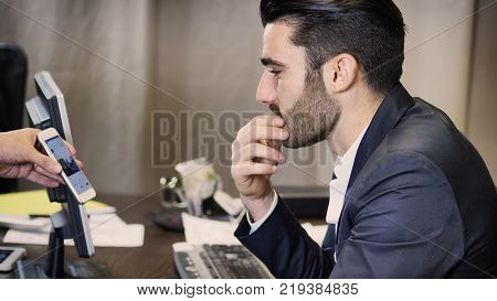 Handsome businessman sitting in his office, talking to client and looking at smartphone that his colleague or client is showing him
