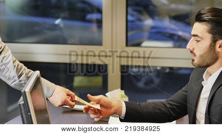 Businessman paying cash money to other man, colleague, collaborator, client or employee