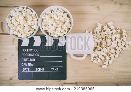 Movie clapper board with coffee cup and popcorn on wooden background