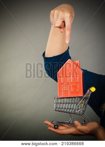 Buying property or home real estate investment concept. Woman holding shopping cart with house inside