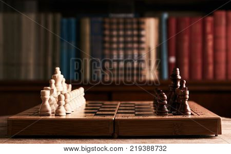 hessboard and chess pieces on a wooden table in a library with books on the bookshelf background, close-up. Education concept
