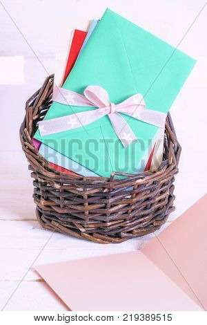 Basket full of letters and a blank message card - Unwritten message card and a wicker basket full of colorful envelopes tied together with pink ribbon and bow on a white wooden background.