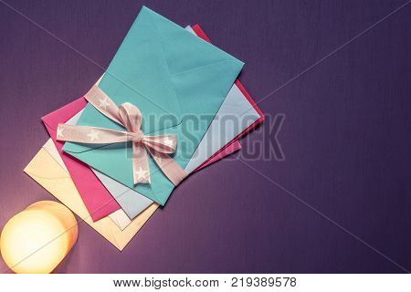 Stack of envelopes tied with bow in candlelight - Bunch of multicolored letters tied together with a pink ribbon and bow and a lit candle near them on a purple wooden background.