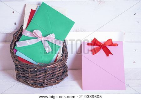 Wicker basket with letters and message card - Pile of multicolored envelopes tied with ribbon displayed in a wicker basket and a paper note with a red bow near it on a white wooden background.