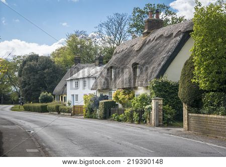 Street view of old thatched cottages in the pretty village of Foxton Cambridgeshire England UK
