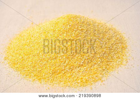 Pile of corn grits on coarse cloth. Close-up image.