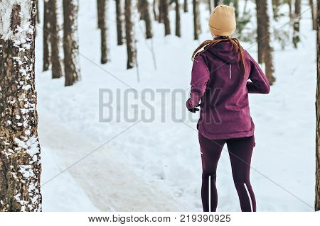 Sports girl runs in the winter in the forest. Active way of life all year round