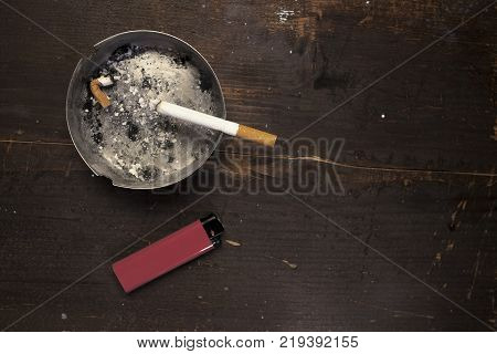 a lit cigarette in a dirty ashtray with a lighter next to the ash tray
