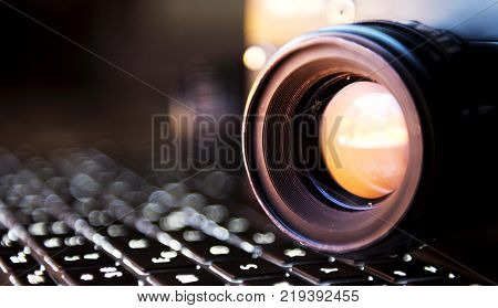 35mm film camera lens isolated standing on computer keyboard