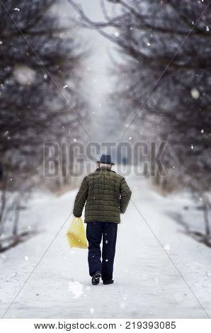 old man with hat walking on snowy winter street