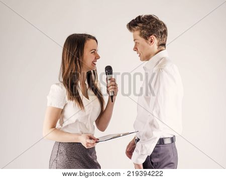 The concept. Young cute guy and girl are talking. The girl is holding a microphone. White background.