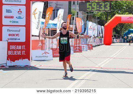 ODESSA UKRAINE - 25 JUN 2017: Excited male runner crossing the finshline of a marathon. Marathon winner at finish. Marathon runner finish line.