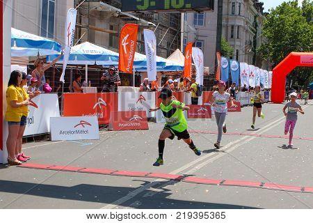 ODESSA UKRAINE - 25 JUN 2017: Children marathon finish line. Marathon runners kids cross finish line at sunny summer day.